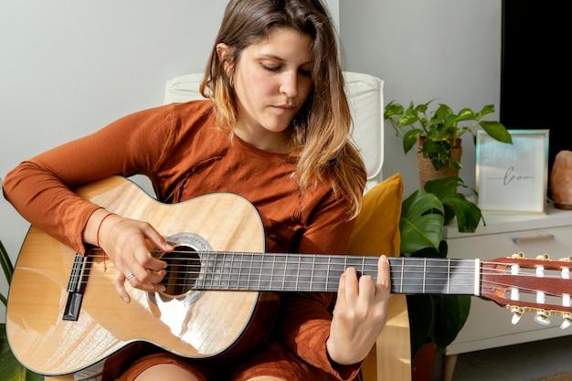 Mulher em casa tocando violão