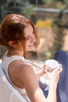 Mulher em casa tomando café