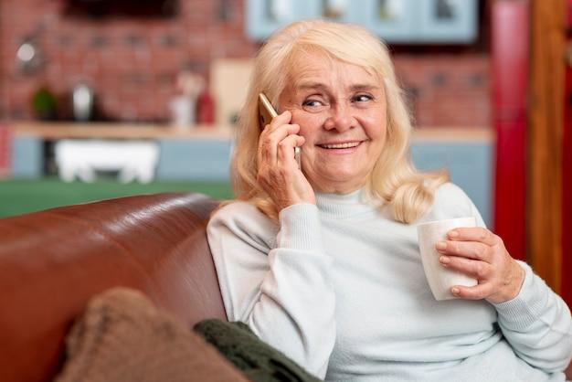 Mulher em casa tomando chá e usando o telefone