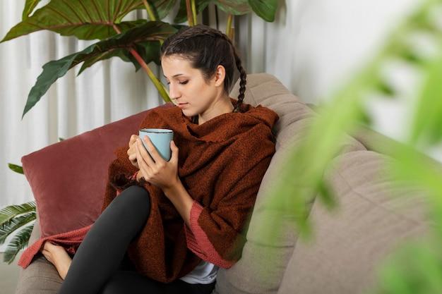 Mulher em casa tomando chá