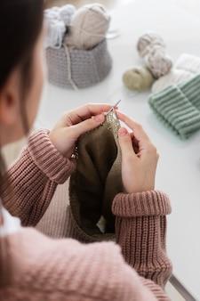 Mulher em casa tricotando de perto