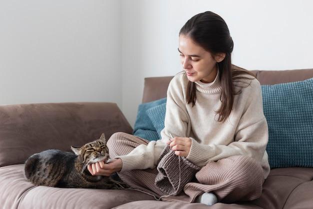 Mulher em casa tricotando e brincando com gato