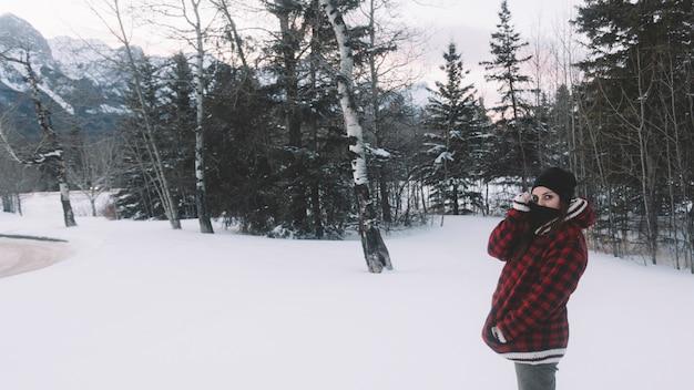 Mulher, em, casaco morno, ligado, árvore pinho, fundo