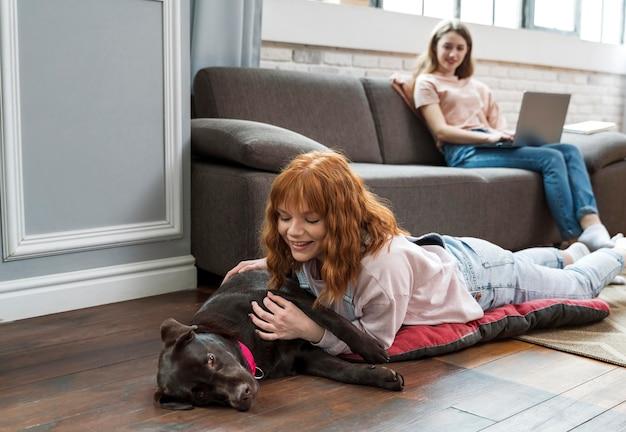 Mulher em cena completa acariciando cachorro no chão