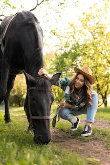 Mulher em cena completa acariciando o cavalo ao ar livre