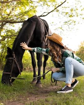 Mulher em cena completa acariciando o cavalo