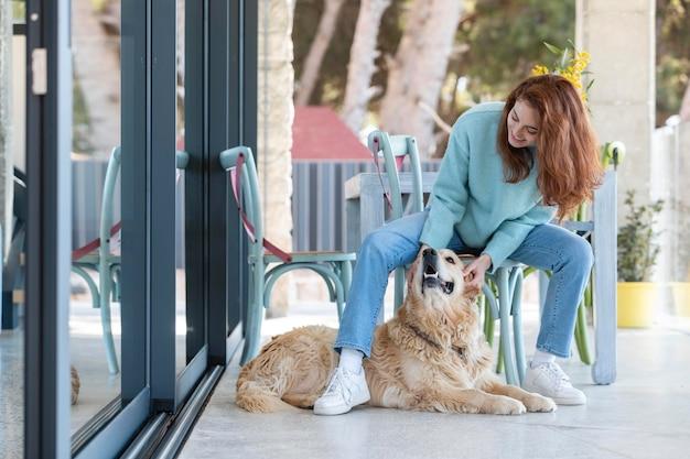 Mulher em cena completa acariciando um cachorro feliz