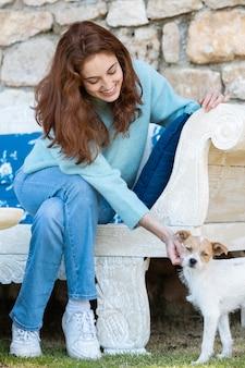 Mulher em cena completa acariciando um cachorro fofo
