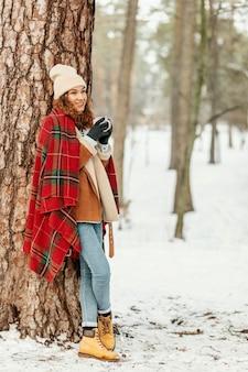 Mulher em cena completa apoiada em uma árvore