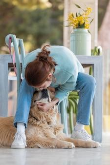 Mulher em cena completa brincando com um cachorro fofo