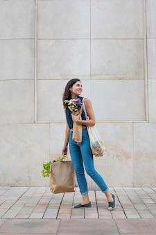 Mulher em cena completa carregando bolsas e flores