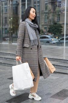 Mulher em cena completa carregando sacolas de compras