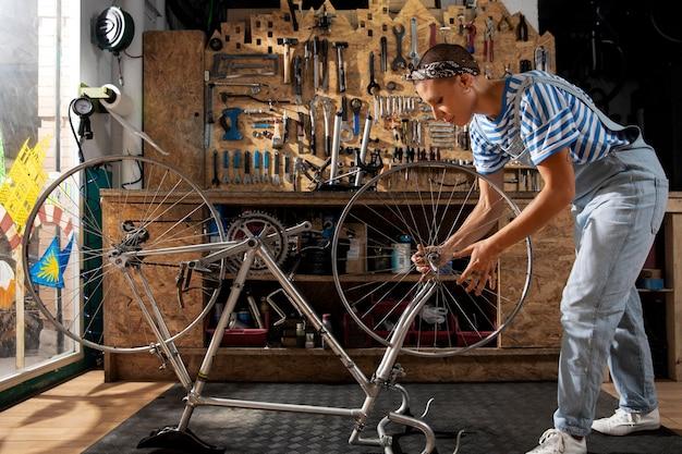 Mulher em cena completa consertando bicicleta