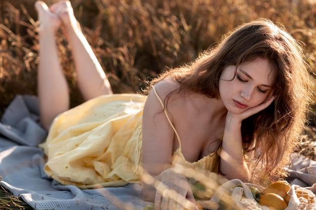 Mulher em cena completa deitada no cobertor