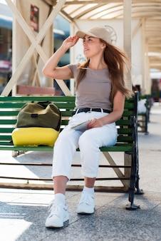 Mulher em cena completa esperando o ônibus na estação