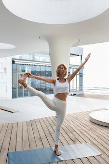 Mulher em cena completa fazendo pose de alongamento ao ar livre