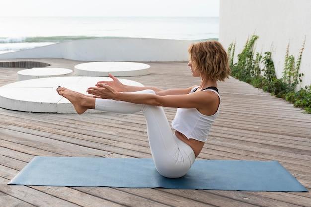 Mulher em cena completa fazendo pose de equilíbrio do lado de fora