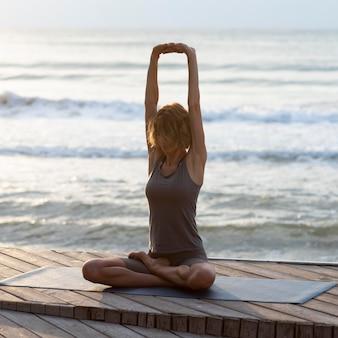 Mulher em cena completa fazendo pose de sukhasana ao ar livre