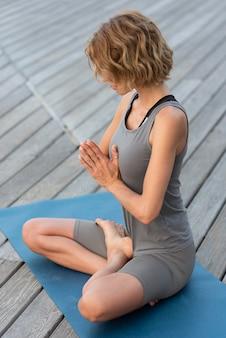 Mulher em cena completa fazendo pose de sukhasana do lado de fora no tatame