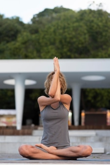 Mulher em cena completa fazendo pose de sukhasana do lado de fora