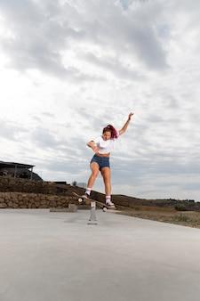 Mulher em cena completa fazendo truques ao ar livre