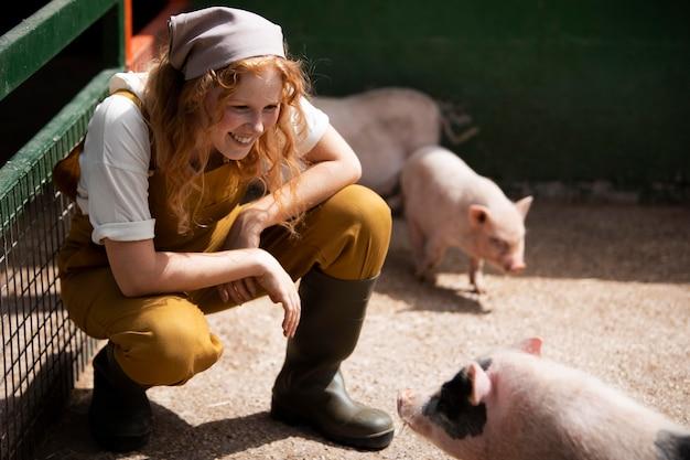 Mulher em cena completa olhando para porcos