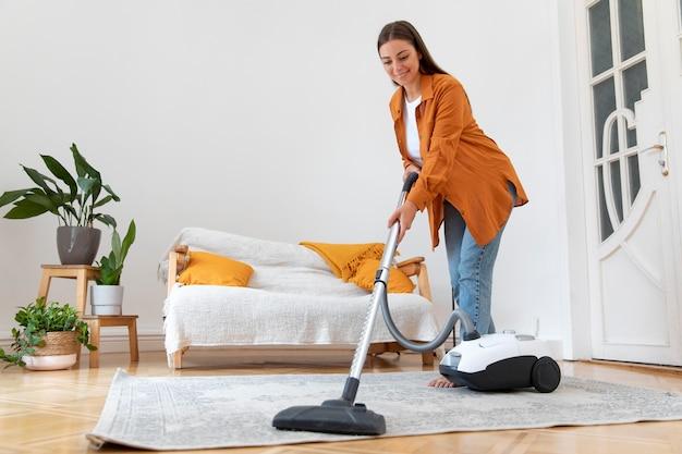Mulher em cena completa passando o aspirador de pó no carpete