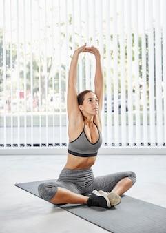 Mulher em cena completa se alongando em uma esteira de ioga