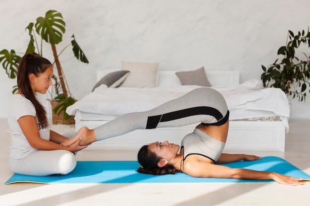 Mulher em cena completa se alongando no tapete de ioga
