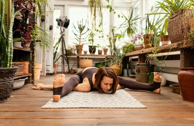 Mulher em cena completa se espreguiçando no tapete