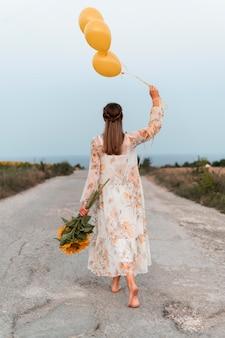 Mulher em cena completa segurando balões e flores