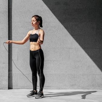 Mulher em cena completa segurando corda de pular