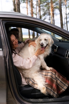 Mulher em cena completa segurando um cachorro