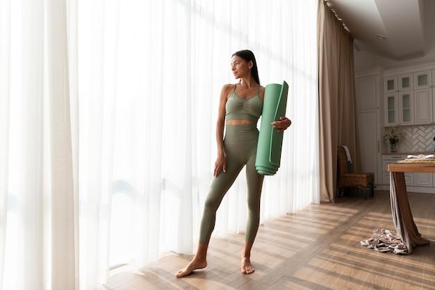 Mulher em cena completa segurando um tapete de ioga