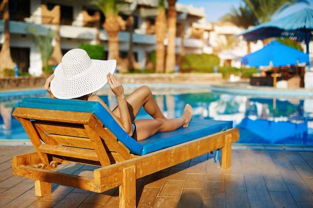 Mulher, em, chapéu branco, mentindo, ligado, um, lounger, perto, a, piscina, em, a, hotel