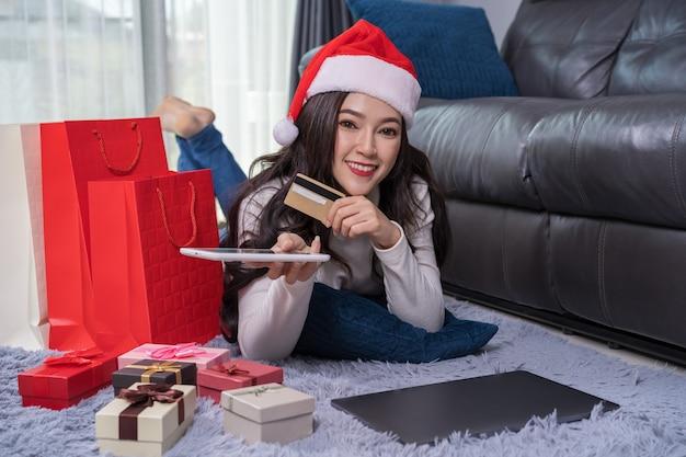 Mulher, em, chapéu santa, comprando online, para, presente natal, com, tablete digital, em, sala de estar