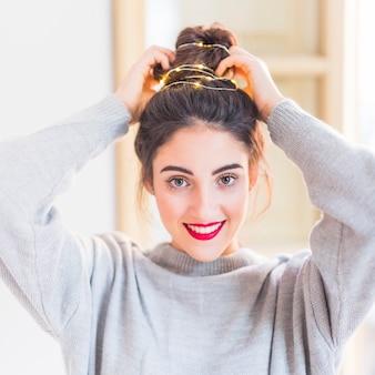 Mulher em cinza com guirlanda de iluminação no cabelo