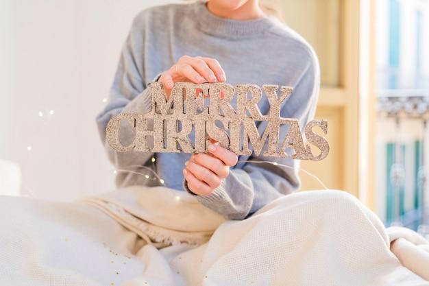 Mulher, em, cinzento, segurando, brilho, inscrição natal feliz
