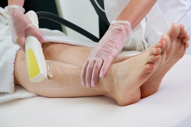 Mulher em clínica de estética profissional durante a depilação a laser
