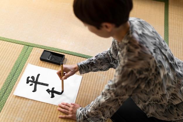 Mulher em close pintando letras japonesas