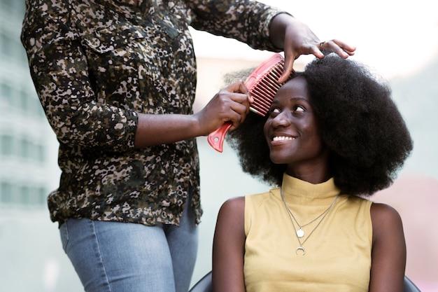 Mulher em close sendo escovada o cabelo