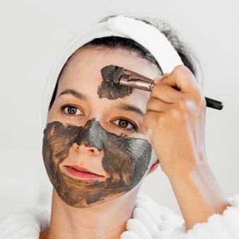 Mulher em close-up aplicando máscara facial orgânica