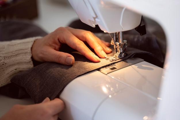 Mulher em close-up costurando uma máquina de costura branca