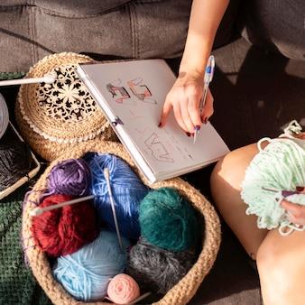 Mulher em close-up fazendo crochê de acordo com a modelo