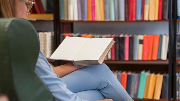 Mulher em close-up lendo uma cadeira