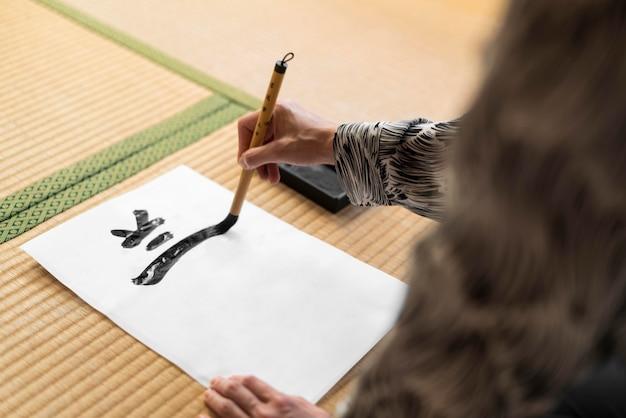 Mulher em close-up pintando carta