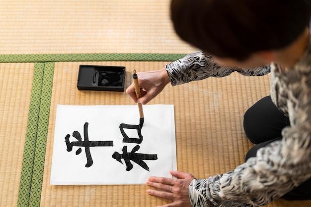 Mulher em close-up pintando letra japonesa