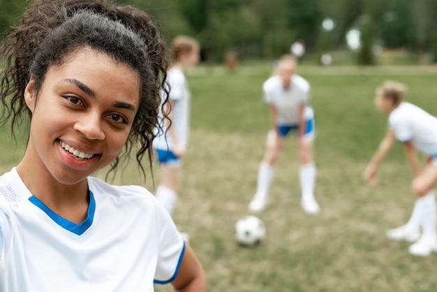 Mulher em close-up posando no campo de futebol