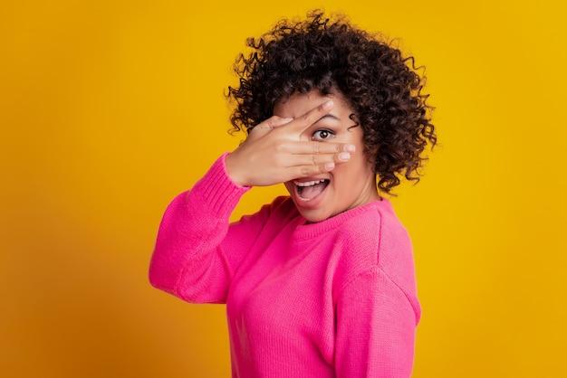 Mulher em closeup retrato espiando por entre os dedos humor animado isolado fundo de parede amarela