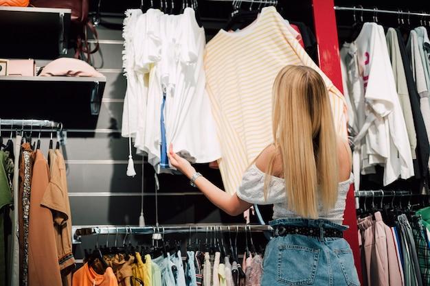 Mulher em compras, checando roupas